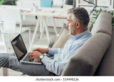 Businessman at home sitting on the couch with feet up and working with his laptop