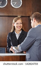 Businessman in hotel paying with credit card at reception