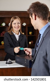Businessman in hotel at reception getting his room key card