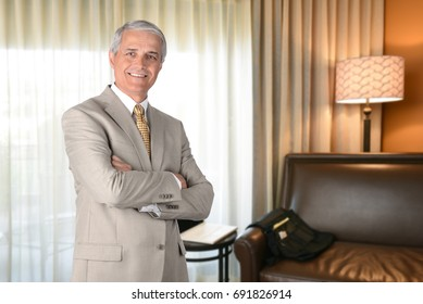 Businessman in hotel room with arms folded and looking at camera. Business travel concept.
