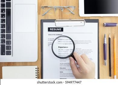 Geschäftsmann oder HR Manager überprüfen einen Lebenslauf auf seinem Schreibtisch mit Magnifier, Computer-Laptop, digitalen Tablet, Taschenrechner und Brille. Informationen mit Vergrößerung wieder aufnehmen. Flat lay.