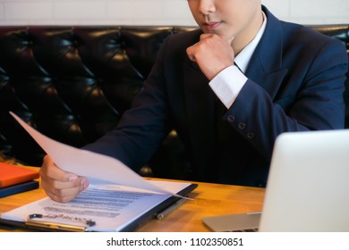 Businessman or HR Manager is reviewing Resume information on his wooden desk. Employment and recruitment concept