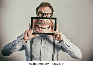 Businessman with huge tablet smile
