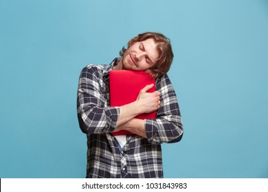 Businessman hugging laptop. Love to computer concept. Attractive male half-length front portrait, trendy blue studio backgroud. Young emotional bearded man. Human emotions, facial expression concept.