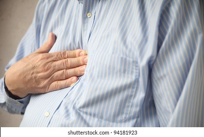 businessman indicates where he feels discomfort from heartburn