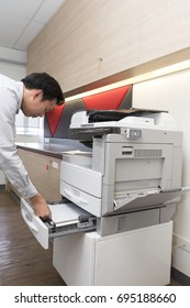 businessman Insert paper into Photocopier at office