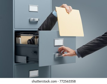 Businessman inside a filing cabinet giving a file to an office clerk: fast file search and efficiency concept