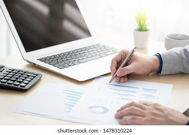 Businessman is inspecting the business reports graphs to audit the financial reports. Analyzing the revenue and auditing the budget concept.