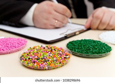 Businessman inspects plastic pellets for industry. Plastic raw materials in granules . Polymer, plastic resin. The dye in the granules of polypropylene and polyethylene.