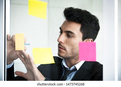 Businessman intend at write on adhesive paper notes on glass wall at workplace , success business concept