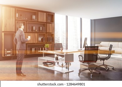 Businessman in interior of ceo office with gray walls, concrete floor, white and wooden computer table and dark wooden shelves with folders. Beige sofa near coffee table. Toned image