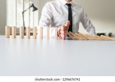 Businessman intervening to stop falling dominos with his hand in a conceptual image.