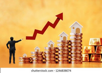 Businessman is introducing a investment as stack coin and wooden home model put on the top and a arrow graph with growing value and gold bar on brown background, Fund of real estate concept.