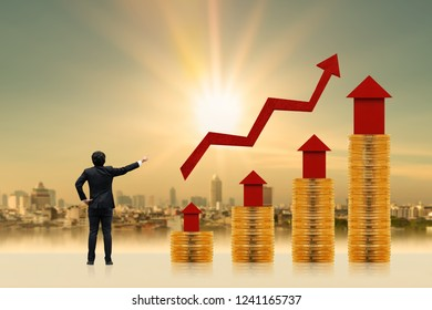 Businessman is introducing a investment as a stack gold coin and red home model put on the top and a arrow graph with growing value on photo blur cityscape background, Fund of real estate concept.