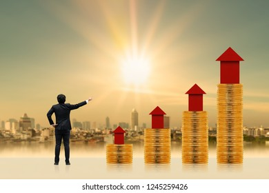 Businessman is introducing a investment as a stack gold coin and red home model put on the top with growing value on photo blur cityscape background, Fund of real estate concept.