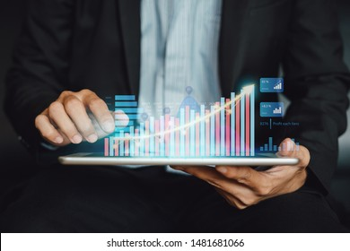 Businessman investor analyzing company financial statistic report working with digital augmented reality graphics technology. Concept for business, economy and marketing fund.
