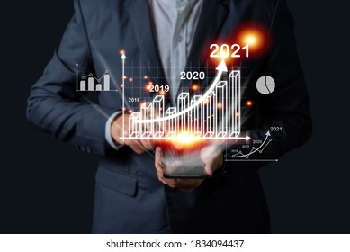 Businessman investor man hand holding trend chart growing up from 2020 to 2021, Business investment growth up concept. - Shutterstock ID 1834094437