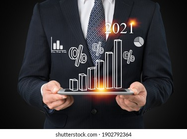 Businessman investor man hand holding trend chart growing up from 2020 to 2021, Business investment growth up concept.