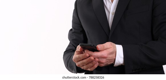 The businessman isolated on white background looks at the smart phone screen.