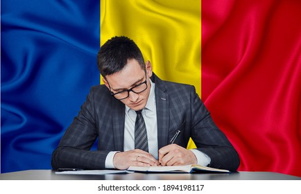 A businessman in a jacket and glasses sits at a table signs a contract against the background of a flag Chad, Chadians,  N'Djamena
