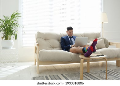 Businessman in jacket and underwear working on laptop at home