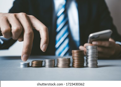 Businessman with Japanese coins and smartphone