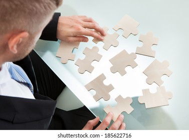 Businessman with a jigsaw puzzle spread out on his desk trying to match the pieces in a concept of problem solving and meeting business challenges  over the shoulder view from above