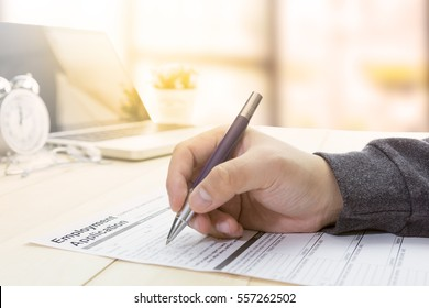 Businessman or job seeker fill in Employment Application form with pen to get a new job. job vacancy concept.