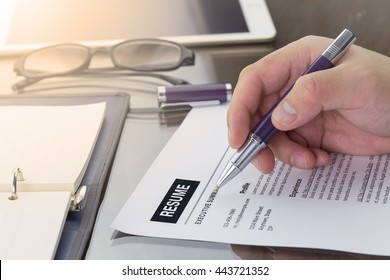 Businessman or job seeker review his resume on his desk before sending to find a new job with pen, notebook, glasses and digital tablet.