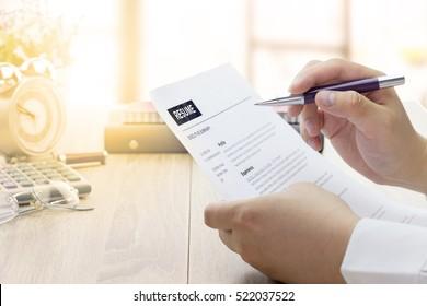 Geschäftsmann oder Arbeitsuchender überprüfen seinen Lebenslauf auf seinem Schreibtisch, bevor Sie eine neue Arbeit mit Füller, Brille und Uhr.