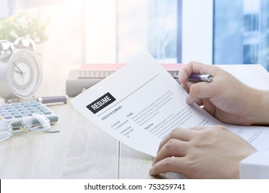 Businessman or job seeker review his resume on his desk before send to finding a new job with pen, necktie, glasses and digital tablet.