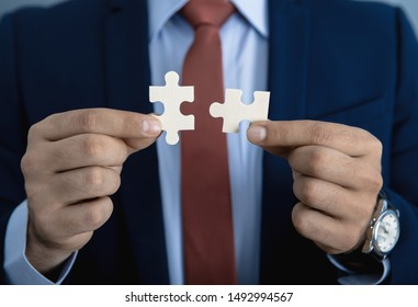 Businessman joining two matching puzzle pieces