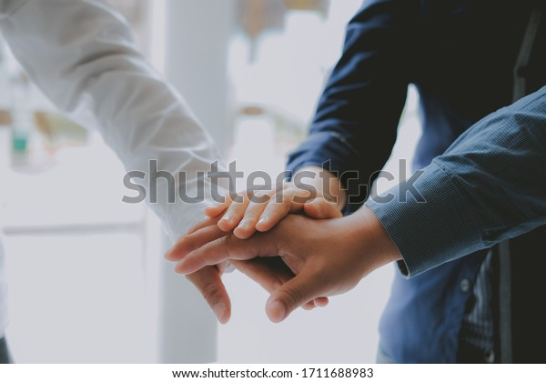 businessman joining united hand, business team touching hands together after complete a deal in meeting. unity teamwork partnership corporate concept.