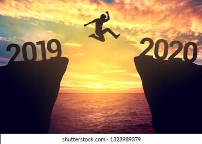 Geschäftsmann springt zwischen 2019 und 2020 Jahren.