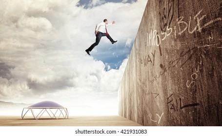 businessman jump over concrete wall