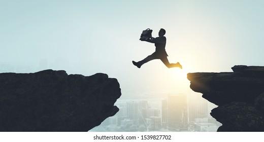 Businessman jump over leap. Mixed media
