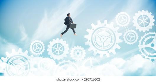 Businessman jumping against blue sky