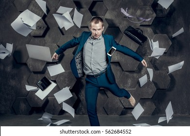 Businessman jumping among floating garments, devices and sheets of paper in the air. The concept of lightness and freedom