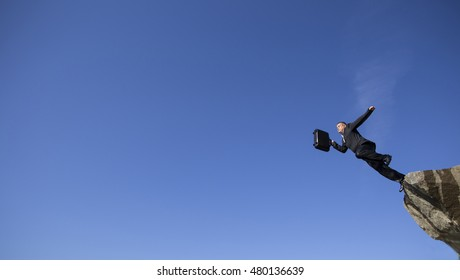Businessman jumping with a briefcase on a background of blue sky.