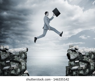 Businessman jumping a gap between cliffs with the sea on the background