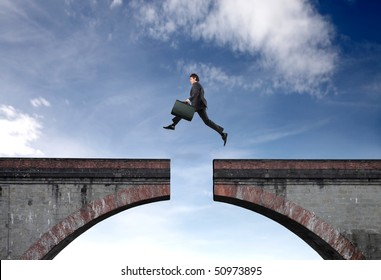 Businessman jumping a gap between two bridge parts