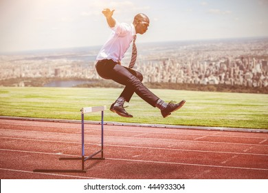 Businessman jumping a hurdle against composite image of racetrack in city