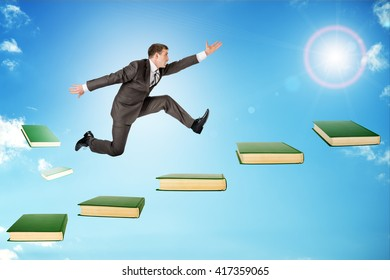 Businessman jumping over books in sky with sun