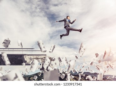 Businessman jumping over gap in bridge among flying papers as symbol of overcoming challenges. Skyscape with sunlight and nature view on background. 3D rendering.