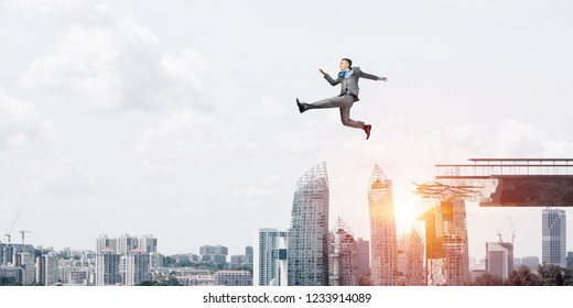 Businessman jumping over huge gap in concrete bridge as symbol of overcoming challenges. Cityscape with sunlight on background. 3D rendering.