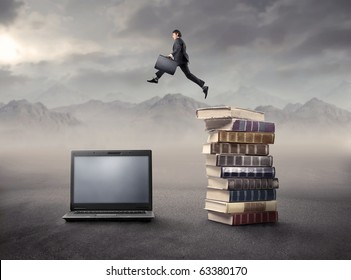 Businessman jumping from some books to a laptop in a desert