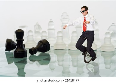 Businessman keeping his balance riding a mono cycle on a chess board