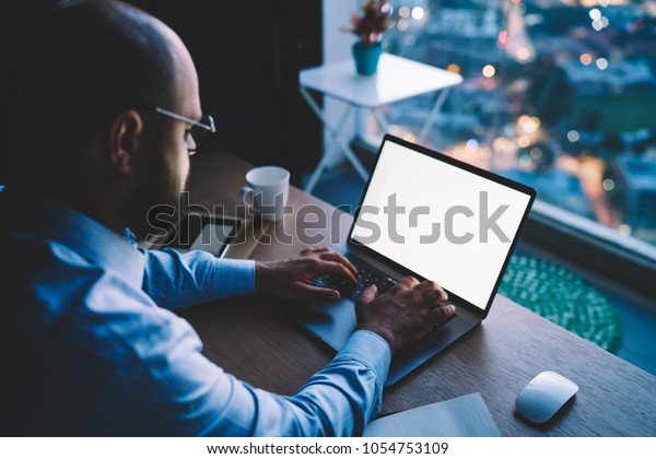 Businessman keyboarding on laptop computer with mock up screen working remotely on report, male entrepreneur making research browsing web page on netbook keyboarding doing distance job late