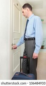 Businessman with keys opening the door of his hotel room