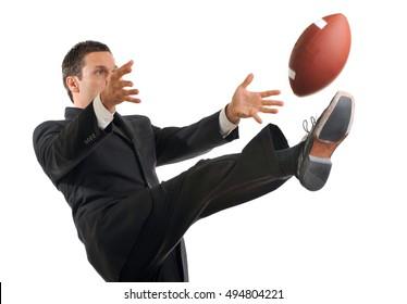 Businessman Kicking American Football on White